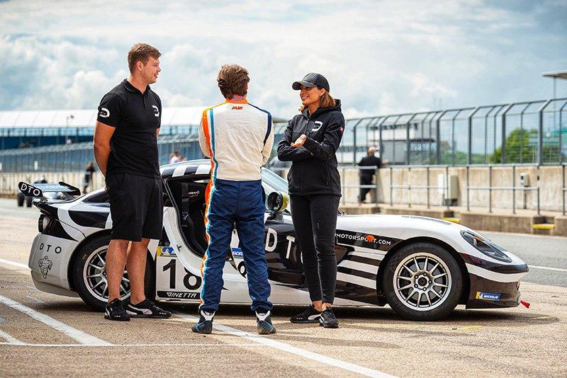 DTO Motorsport staff standing with DTO Ferrari Ginetta