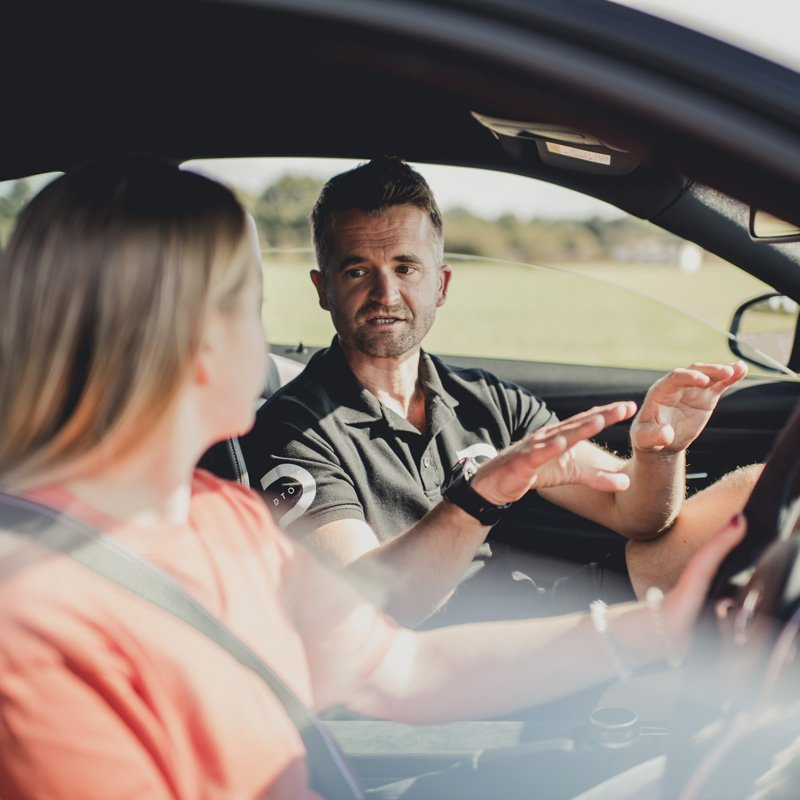 DTO MOTORSPORT instructor photographed inside a car teaching someone how to drive